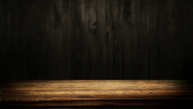 Old wood table with dark brown wall blurred background.