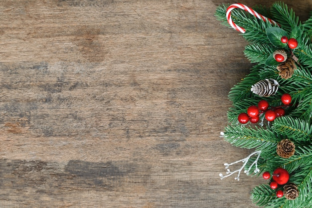 Old wood texture decorate with pine leaf, pine cones, holly balls  and candy cane in christmas theme concept