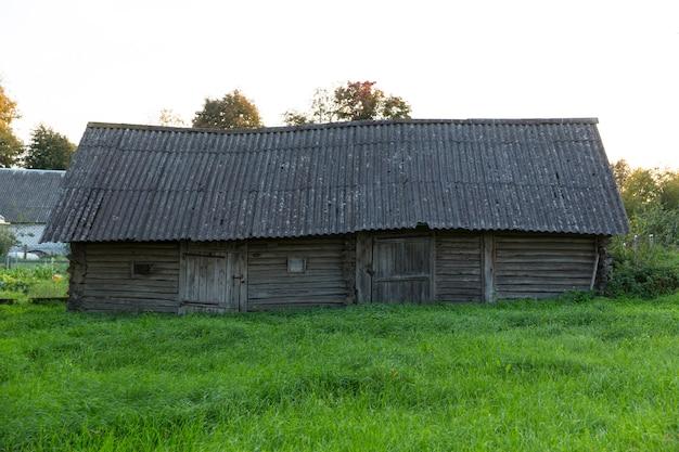 Старый деревянный заброшенный деревенский дом. лето, зеленая трава и деревья, скворечник. фото высокого качества