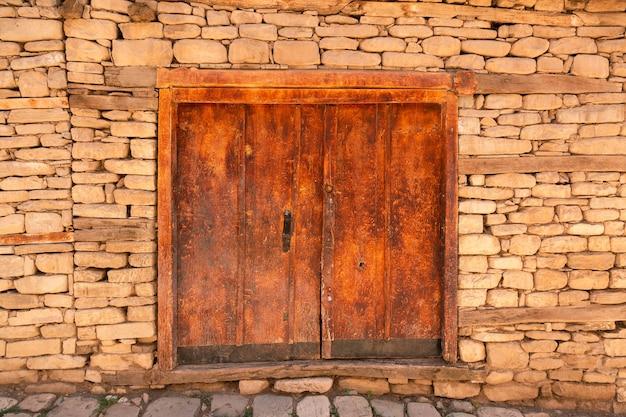 石の壁にある古い木製の古代のドア歴史的な町の通り
