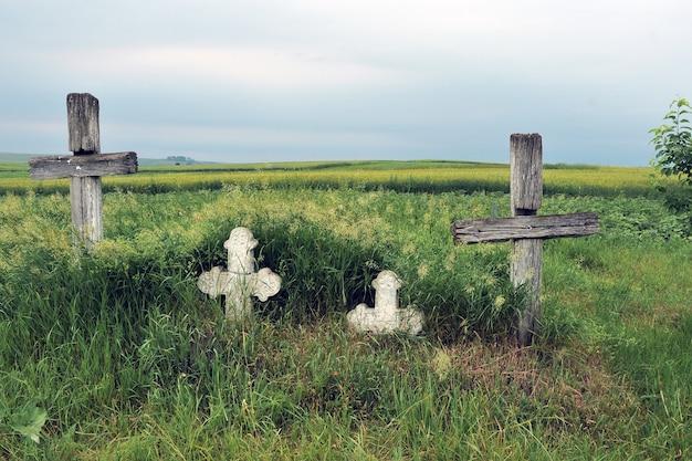 Старые деревянные и каменные кресты на могилах заброшенного кладбища
