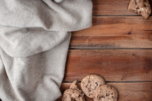 Old wooden background and knitted warm pullover. autumn decor and biscuit liver with chocolate. free space for text. top view.copy space