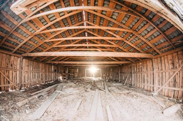 古い干し草でいっぱいの古い木造の納屋で、木の板を通して光が輝いています。