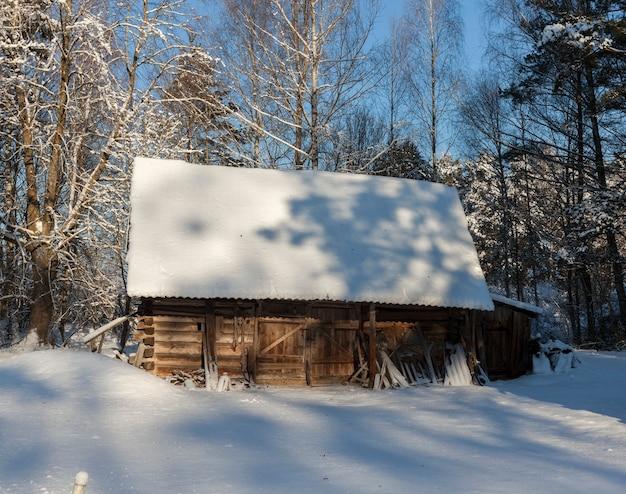 숲의 영토에 위치한 오래 된 나무 헛간. 겨울 시즌.