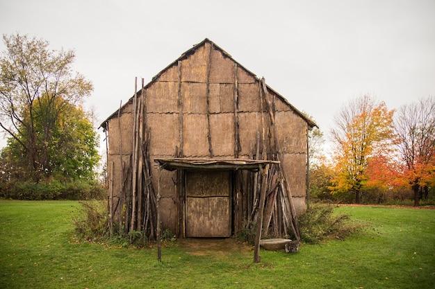 昼間の曇り空の下の野原の木々に囲まれた古い木造の納屋