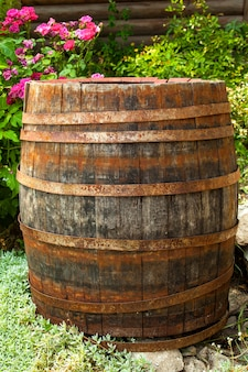 庭のピンクの花に囲まれた古い木樽