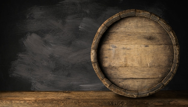 Old wooden beer barrel on the dark background.