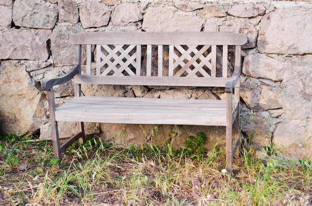 Old wooden bench near a stone fence.