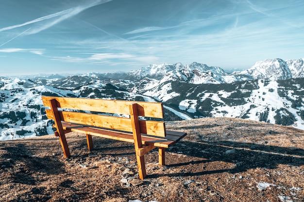Vecchia panca in legno sulla cima di una scogliera con bellissime montagne rocciose ricoperte di neve