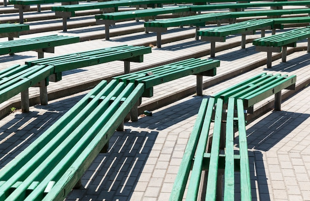 Old wooden benches of green color, old benches located in a summer amphitheater without a roof