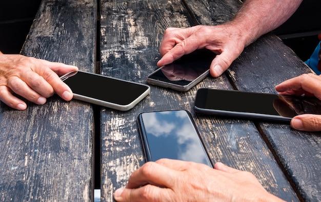휴대 전화를 들고 인간의 손의 그룹과 함께 오래 된 나무 검은 테이블. 우정과 공유의 개념입니다. 백인 민족입니다.