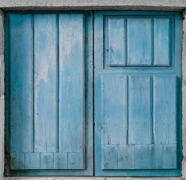 Старая деревянная синяя дверь в старой каменной стене