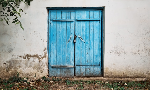 Old wooden blue door in an old wall with crumbling plaster