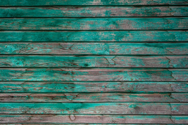 Old wooden boards with peeling green paint. the green paint will come off the wooden planks. green paint with old wooden surface