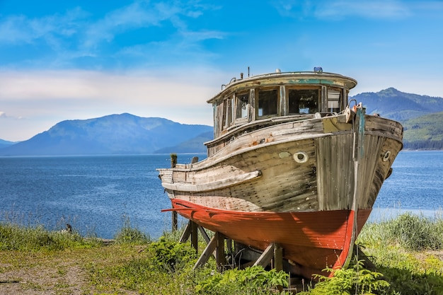 Old wooden boat on land in front of alaskan mountains