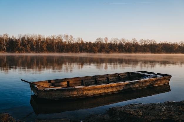 Старая деревянная лодка на воде спокойного озера на рассвете