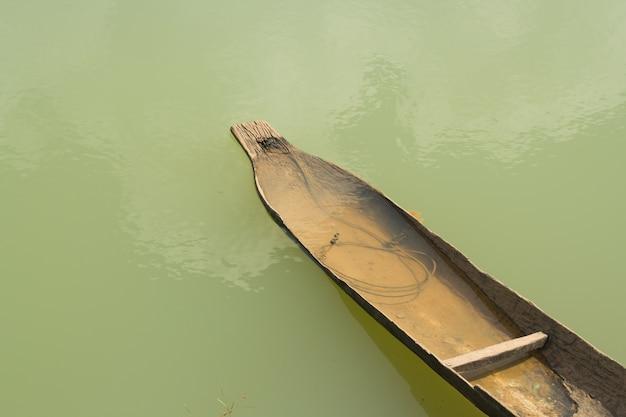 Old wooden boat in pond.