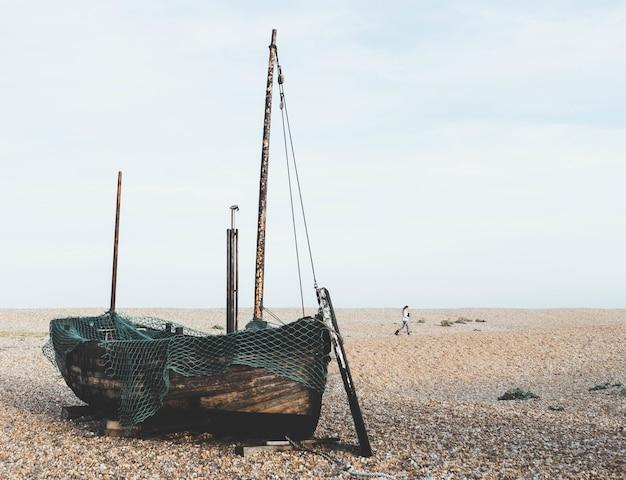 Vecchia barca di legno sulla sabbia dietro una donna