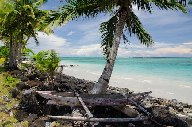 Vecchia barca di legno sulla riva circondata dal mare e dalle palme nell'isola di savai'i, samoa
