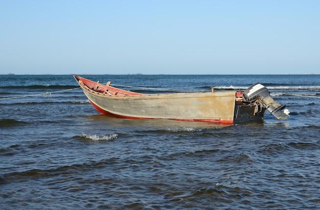 Старая деревянная лодка с бензиновым двигателем на берегу моря