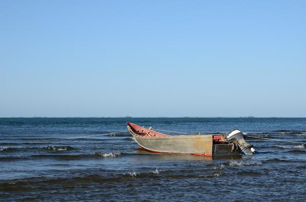 바다로 가솔린 엔진을 가진 오래 된 나무 보트