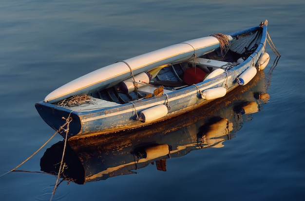 An old wooden boat with a kayak lying on it on the water of lake garda.