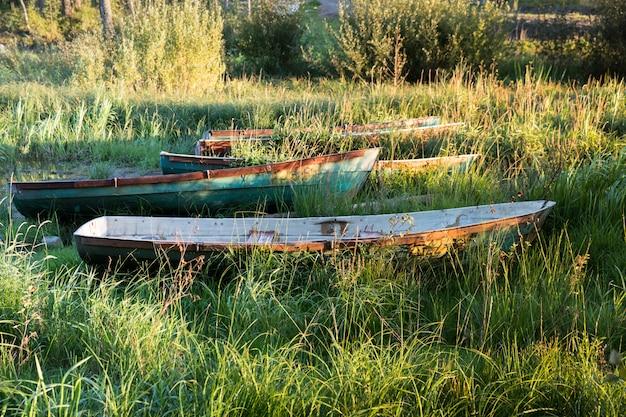 夕暮れ時の草で草に覆われた海岸に古い木造船