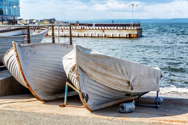 Старые деревянные лодки на берегу на городской набережной.