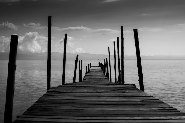 Old wooden bridge cross path to sea.