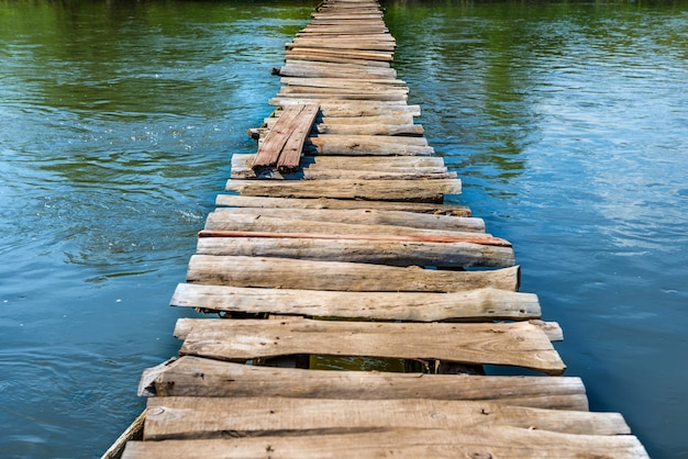 川のほとりに緑の木々がある川を通る古い木製の橋