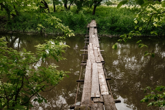 Old wooden bridge, wooden bridge across a small river, bridge with nature.