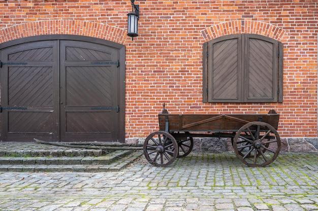 Старая деревянная тележка у стены из красного кирпича с воротами, ставнями и фонарем
