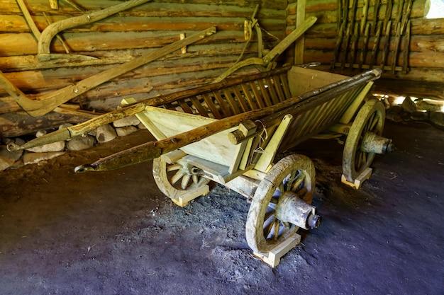 Старая деревянная тележка для перевозки материалов в поле.