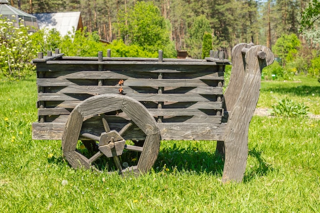 Старая деревянная тележка на зеленом лугу