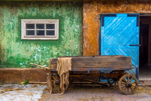 Old wooden cart in the village on the background of an old house. large blue wooden gate.
