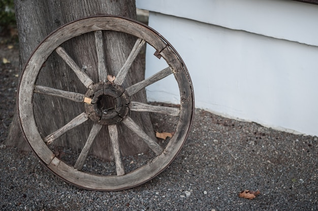 An old wooden cartwheel stands at the wall of the house.