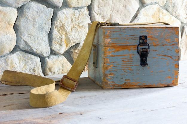 Old wooden case on a tarpaulin belt near a stone wall closeup