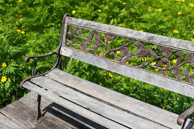 緑豊かな庭園の屋外、フラワーガーデン(コスモスの花)の古い木の椅子