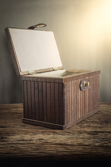 Old wooden chest with open lit on wooden tabletop against grunge wall