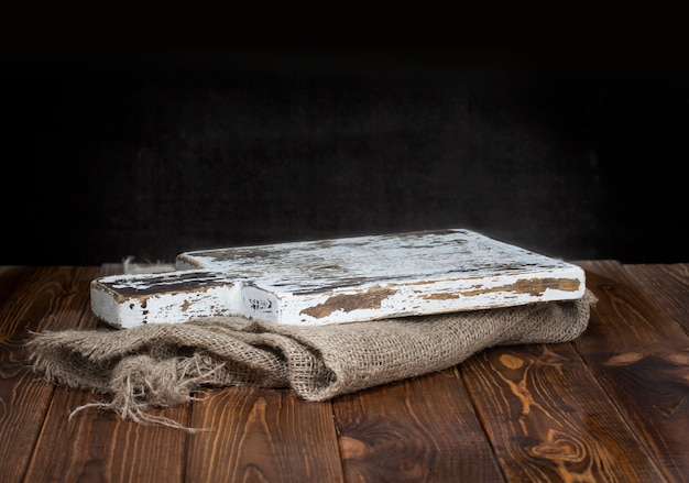 Old wooden chopping board with burlap tablecloth