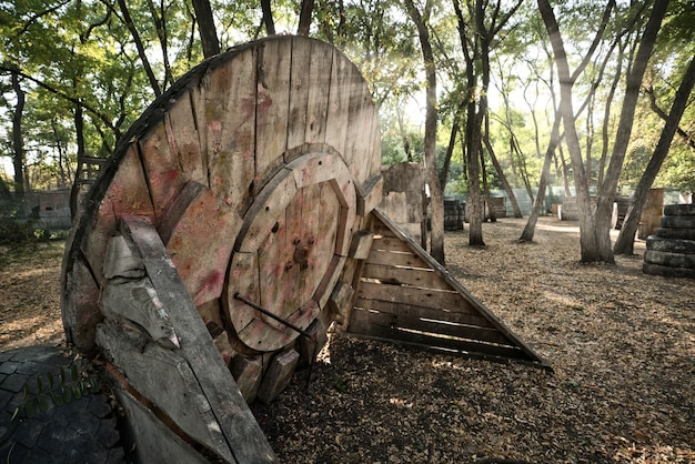 An old wooden circular building at the base for a paintball game, behind which players are hiding in search of rescue