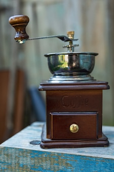 An old wooden coffee grinder on a blue bench. close-up. vertical.
