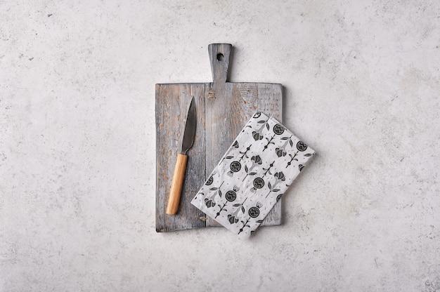 Старая деревянная разделочная доска с ножом и крафт-бумагой на сером текстурированном фоне концепции для изготовления