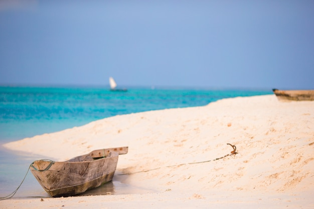 Old wooden dhow on white beach in the indian ocean