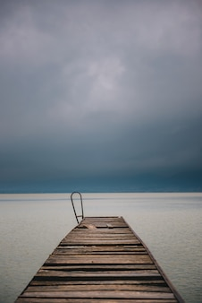 Old wooden dock in summer stormy weather