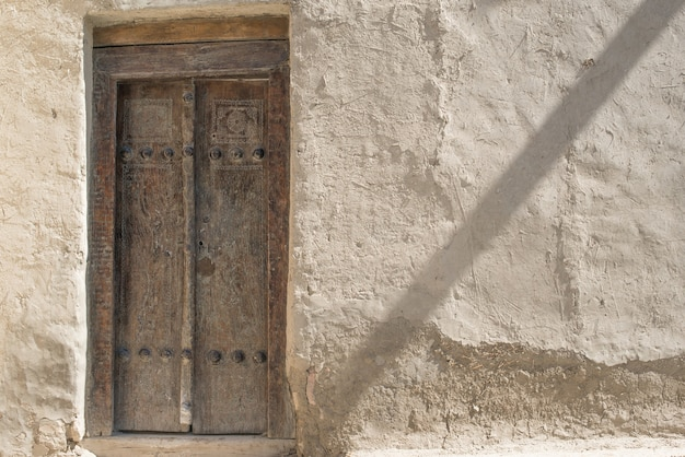 Old wooden door and exfoliating wall in the historic city, central asia Premium Photo