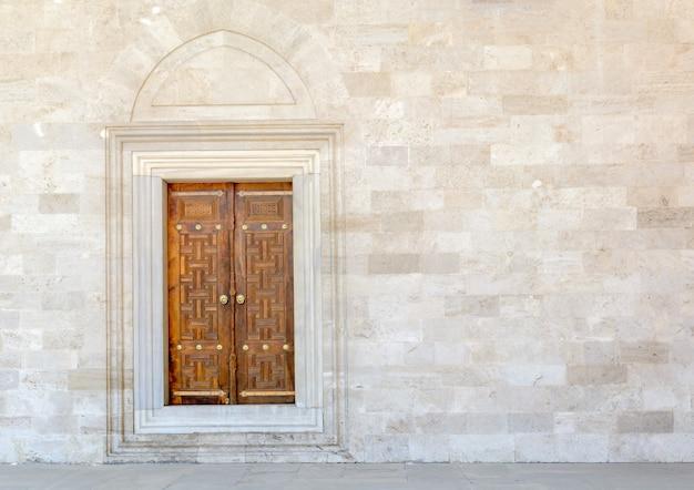 Old wooden door on grunge sandstone wall.