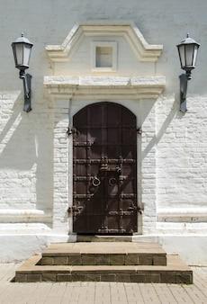 古い木製のドアの石の壁。城の裏口。
