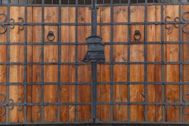 단조 경첩이 있는 오래된 나무 문, 단조 요소가 있는 오래된 문의 나무 질감