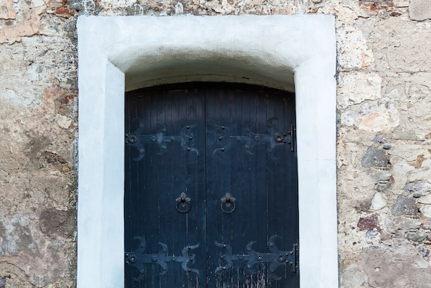 Old wooden door with forged hinges, wooden texture of old doors with forging elements